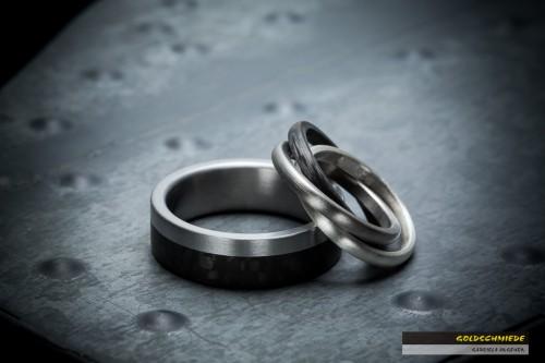 Der Damenring sticht hier besonders ins Auge. Er besteht aus drei ineinander verschachtelten Ringe aus drei Materialien: Carbon, Titan und Silber.